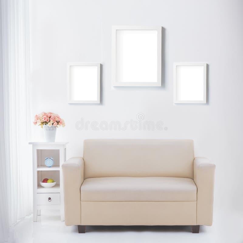 Vardagsrum med den tomma affisch- eller fotoramen royaltyfri fotografi
