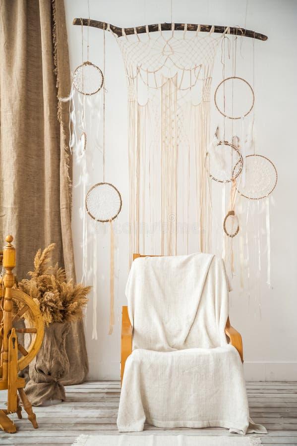 Vardagsrum med en lantlig fåtölj Retro stol, spindel, makramé på väggen i rummet Detaljer av en ljus skandinavisk interio royaltyfri fotografi