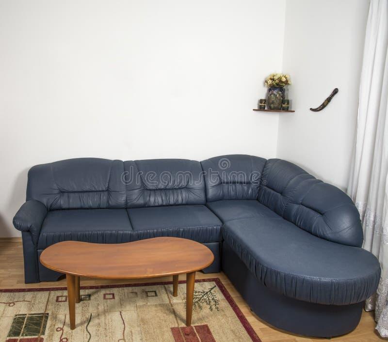 Vardagsrum med en soffa och en liten tabell royaltyfri bild