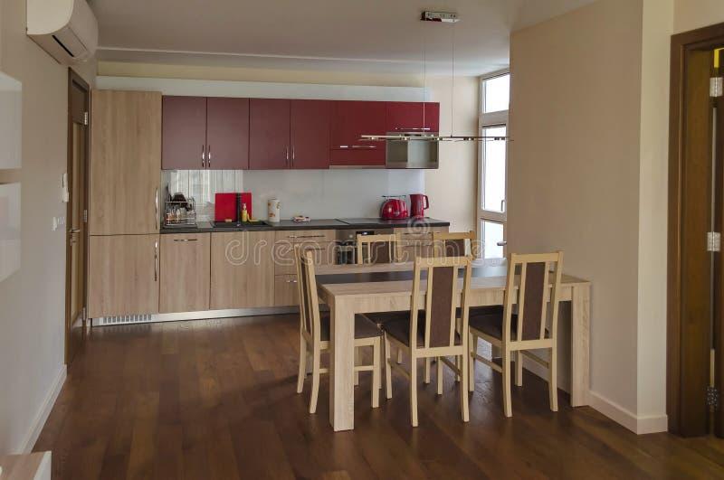Vardagsrum med kökplatsen och matbord i renoverad lägenhet arkivbilder