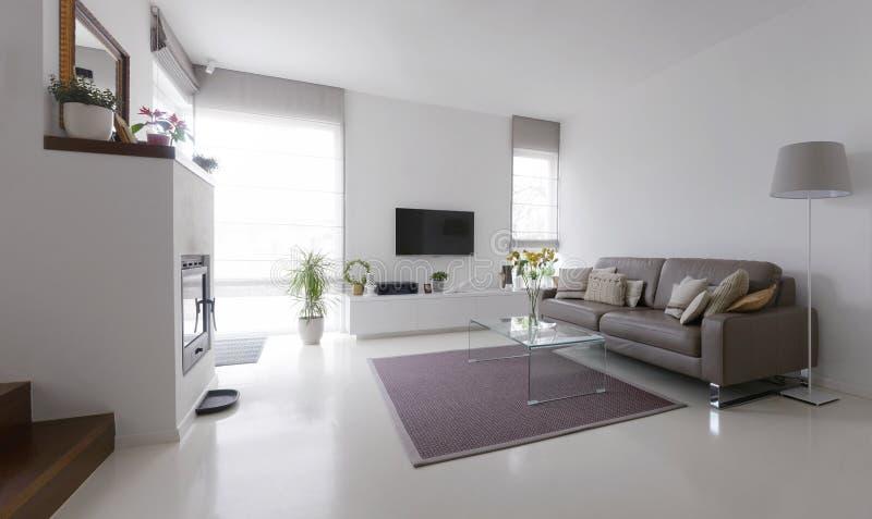 Vardagsrum med lädersoffan och exponeringsglastabellen royaltyfri fotografi