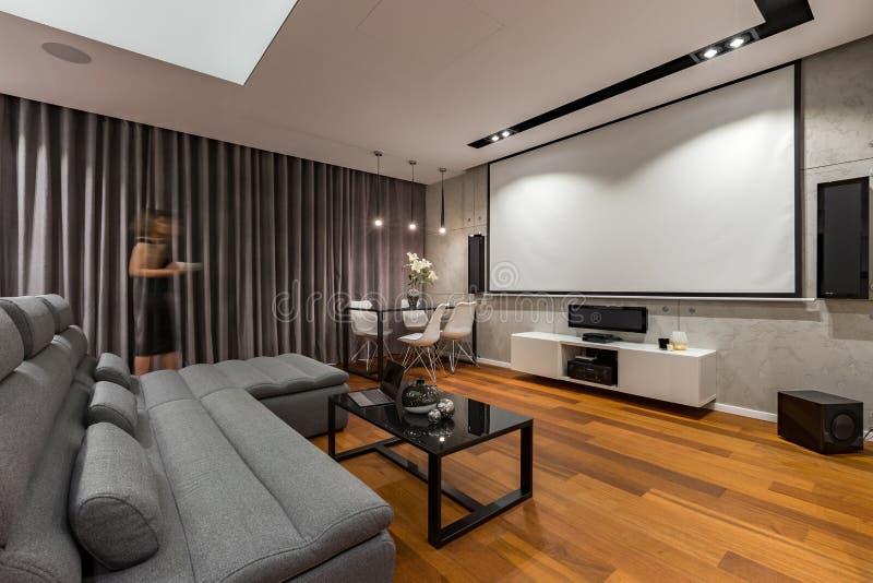 Vardagsrum med projektorskärmen arkivbild