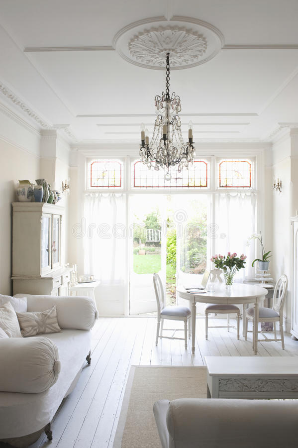 Vardagsrum med soffan, tabellen, stolar och ljuskronan arkivbild