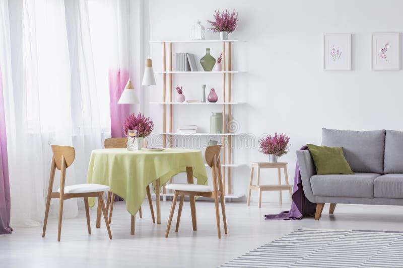 Vardagsrum med trästolar, den runda tabellen med den olivgröna gröna bordduken, den gråa soffan med kudden och ljung i krukor royaltyfria foton