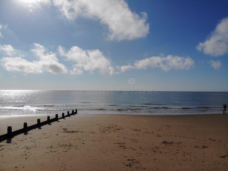 Vare el frinton tranquilo hermoso de essex de los sky's de las nubes del mar de las olas oceánicas de la arena azul de la ingle imagenes de archivo