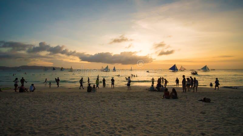 Vare en la isla de Boracay en los rayos de la puesta del sol de la tarde Siluetas de la gente que juega una bola en la playa y imagen de archivo