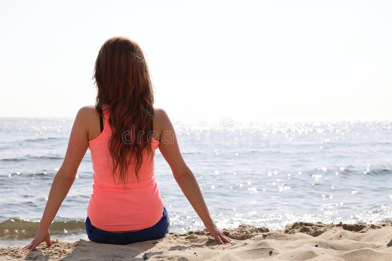 Vare a la mujer de los días de fiesta que goza de la arena que se sienta del sol del verano que mira la ha fotos de archivo libres de regalías