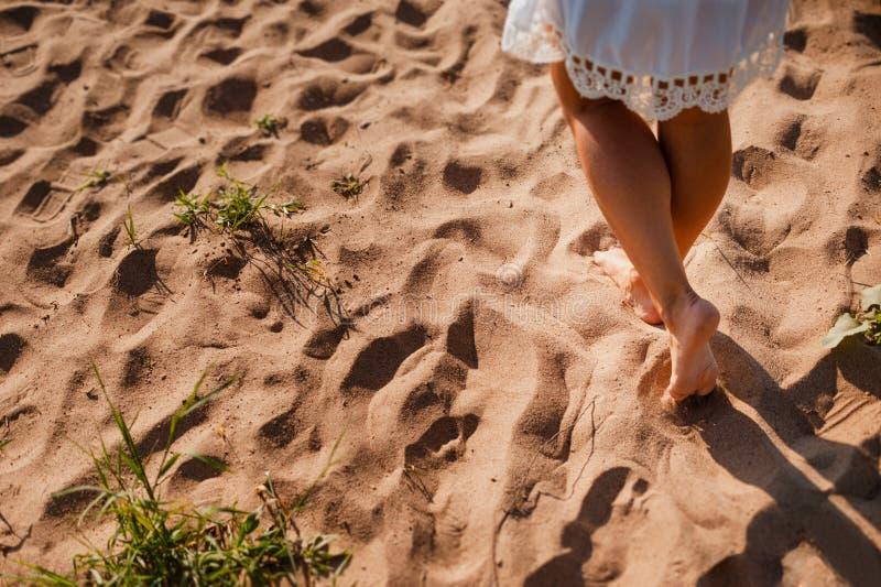 Vare a la mujer del viaje que camina en las huellas que se van arenosas en la arena Ciérrese encima del detalle de piernas femeni foto de archivo libre de regalías