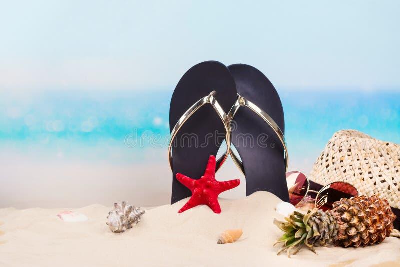 Vare las chancletas, el sombrero y las gafas de sol en la playa arenosa hermosa cerca del océano Copie el espacio foto de archivo libre de regalías