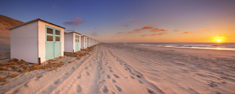 Vare las chozas en la puesta del sol, isla de Texel, los Países Bajos imagen de archivo