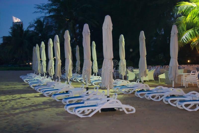 Vare los muebles, los paraguas cerrados y los salones, sistema en una playa tailandesa lluviosa a finales de la tarde fotografía de archivo