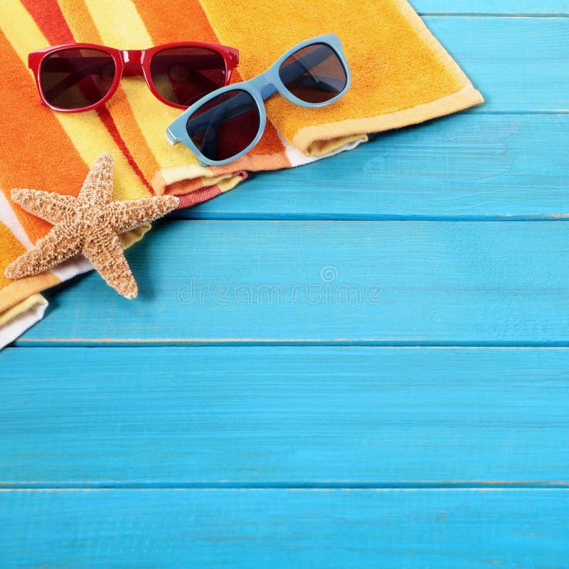 Vare tomar el sol tropical del decking de la frontera del fondo de las gafas de sol de los pares de madera azules de la toalla imágenes de archivo libres de regalías