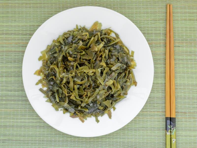 Varech mariné coupé en tranches d'un plat blanc et des baguettes sur un tapis de table en osier vert L'algue comestible contient  image stock