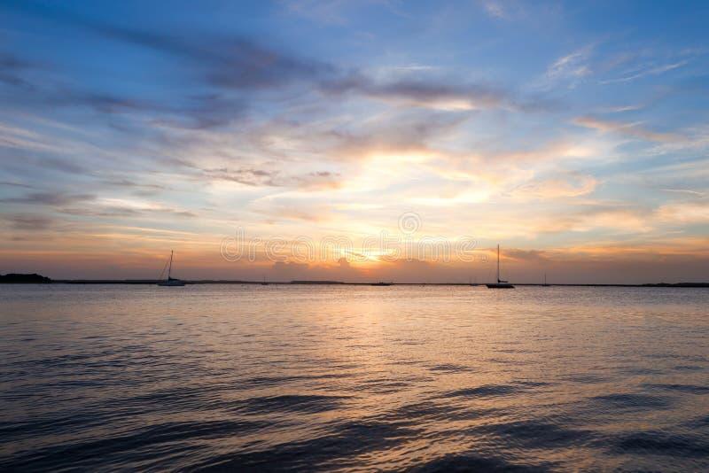 Varend bootsilhouet over zonsonderganghemel royalty-vrije stock fotografie