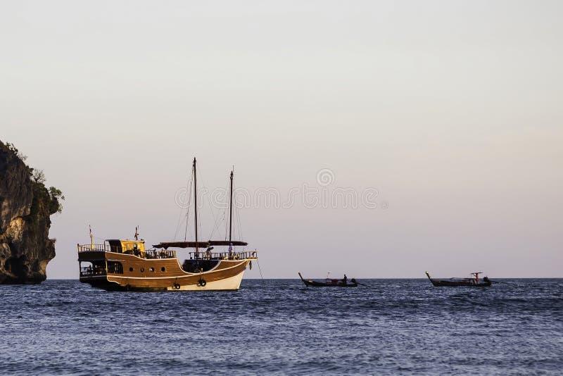 Varend houten schip in de oude stijlzeilen op het overzees Dichtbij er zijn twee kleine boten op lange afstand royalty-vrije stock afbeeldingen