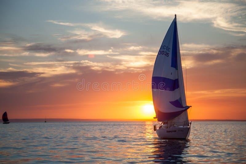 Varend jacht bij zonsondergang stock afbeelding