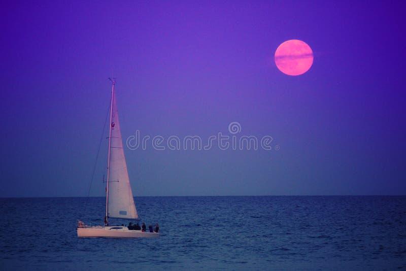 Varende boot en volle maan royalty-vrije stock afbeeldingen