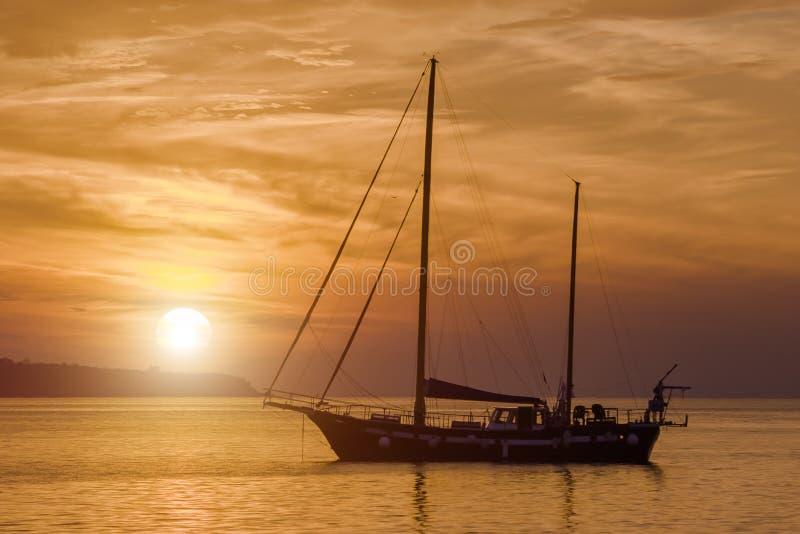 Varende boot en zonsondergang royalty-vrije stock afbeelding
