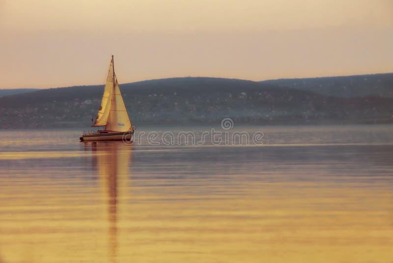 Varende boot op het meer bij zonsondergang stock afbeeldingen
