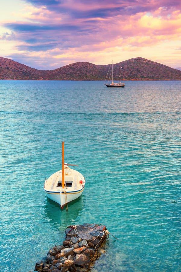 Varende die boot in de vreedzame golf van Elounda, Kreta wordt verankerd stock foto's