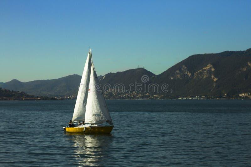 Varende die boot op een meer met bergen wordt omringd royalty-vrije stock foto