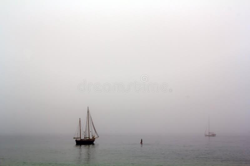 Varende schip en peddelsurfer in een nevelige dag royalty-vrije stock afbeeldingen