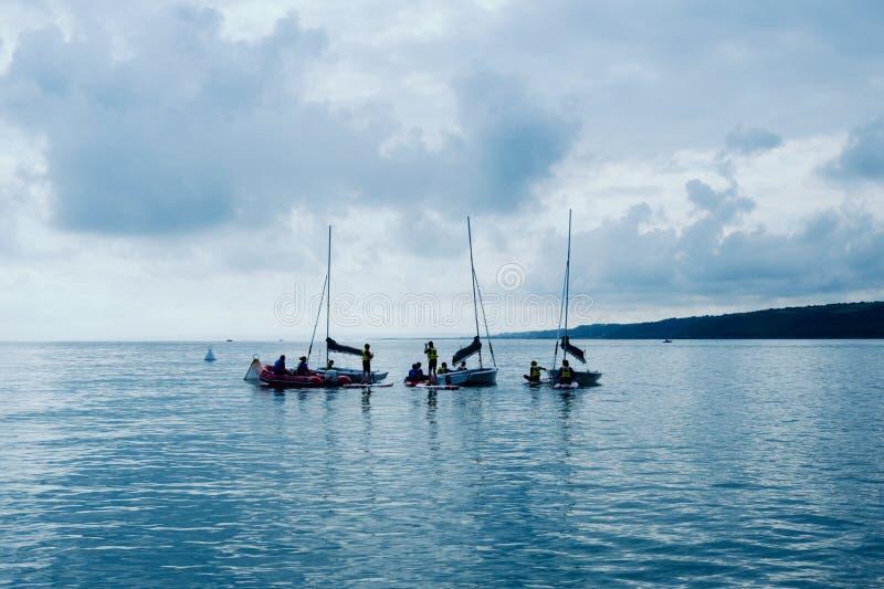 varende school voor jonge geitjes die bij de baai met kalm vlak water en weinig wind praktizeren stock foto's