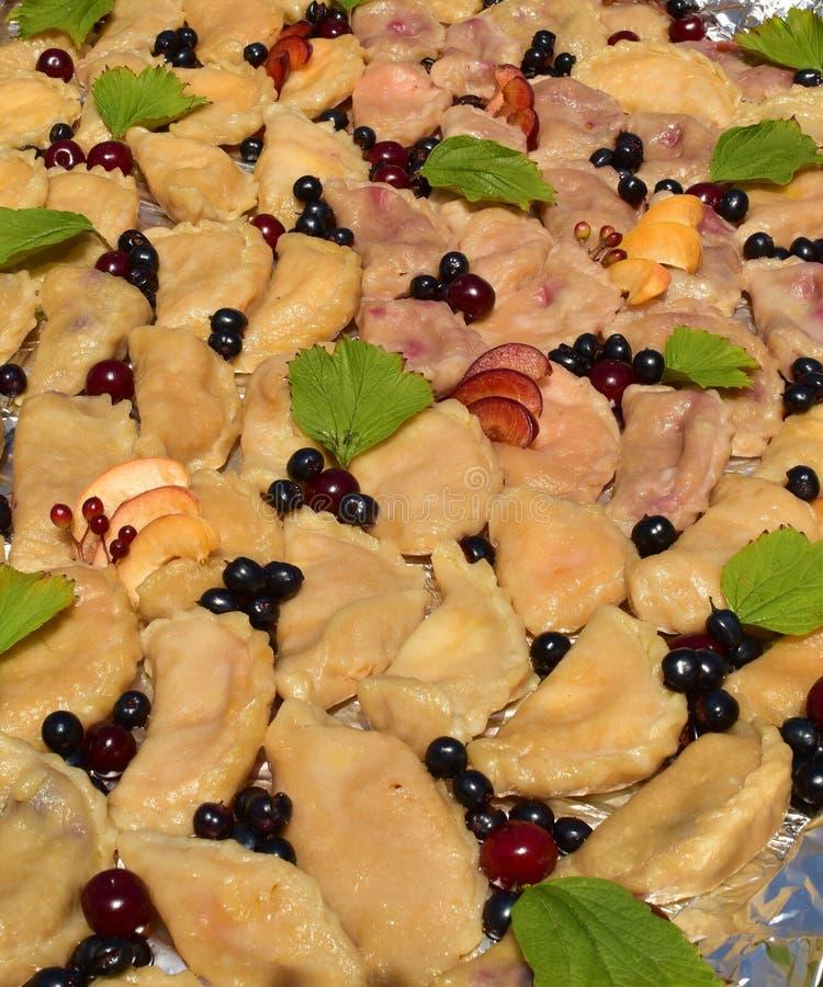 Vareniki con cerezas, vareniki con patatas, vareniki con rizo, vareniki ruso vareniki, cerezas, productos para la masa foto de archivo