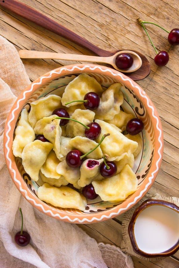 Vareniki ucraniano das bolinhas de massa do russo tradicional caseiro com a cereja no prato cerâmico foto de stock