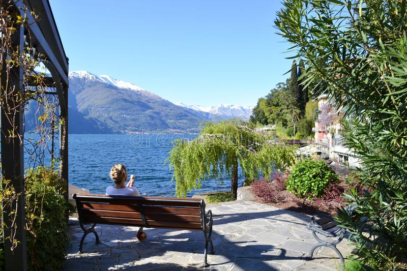 Young lady eating an ice-cream sitting on a bench at the lake Como lakefront in a beautiful sunny spring day. stock photo