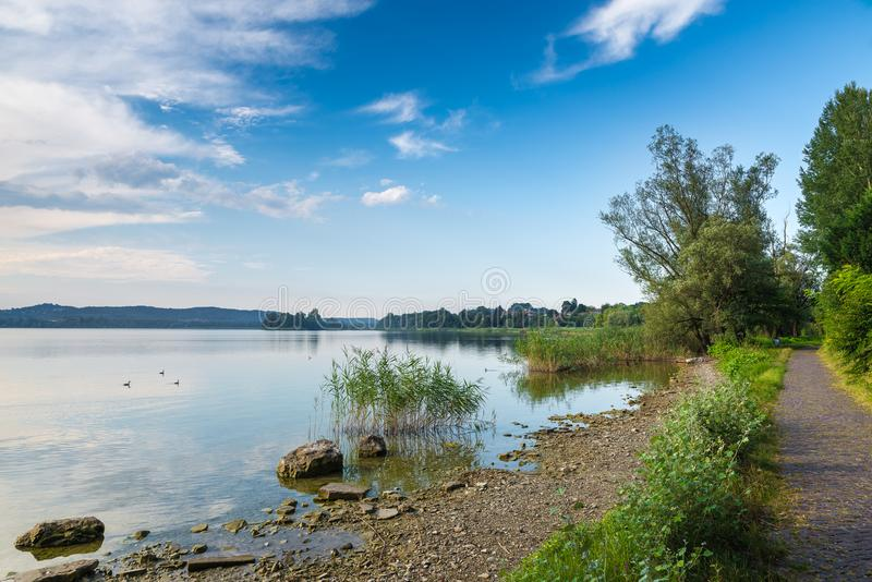 Varese Lake with Virginia islet and a stretch of the pedestrian cycle track around the lake, Biandronno, Italy stock photography