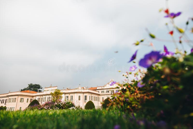 Varese OUTUBRO DE 2018 ITÁLIA - flores contra o palácio de Estense, ou Palazzo Estense imagem de stock royalty free