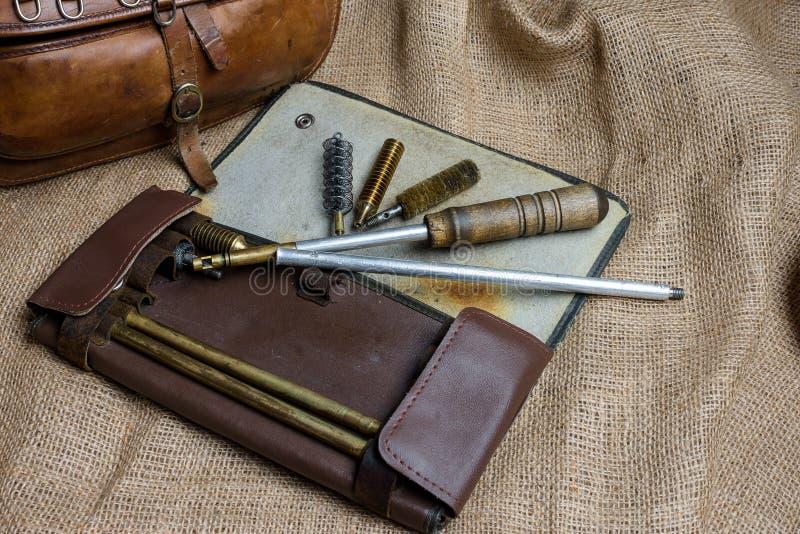 Vareta de espingarda para o saco de limpeza da arma e da caça no baground velho de pano fotos de stock