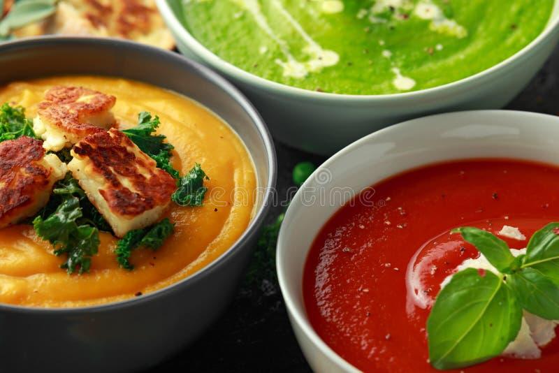 Variété de bols de soupe crèmes : pois et menthe douce, tomate et courge de basilic et de butternut avec le chou frisé cuit à la  photo stock