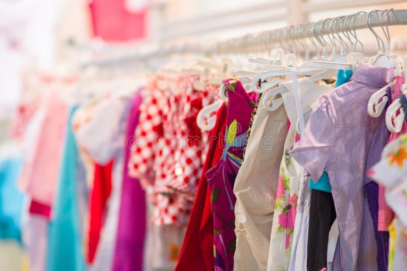 Variété de chemises, pantalons, robes dans le mail de gosses image stock