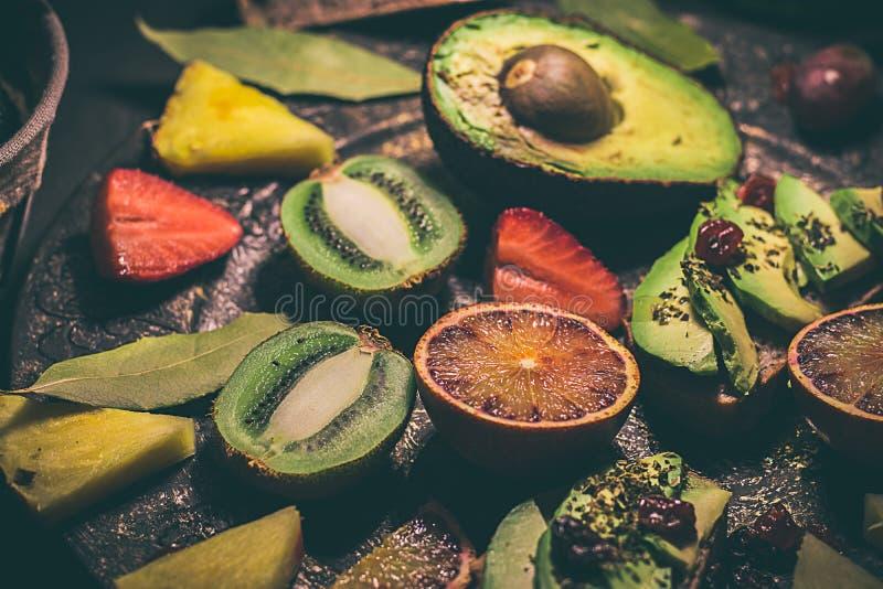 Variété de fruits, d'avocat, d'oranges sanguines, d'ananas, de kiwi, de fraises et de raisins photos stock
