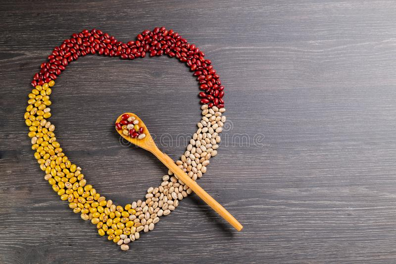 Variété de haricots sur la cuillère en bois sur le fond en bois fèves de mung, arachides, haricots rouges et haricots bruns photographie stock libre de droits