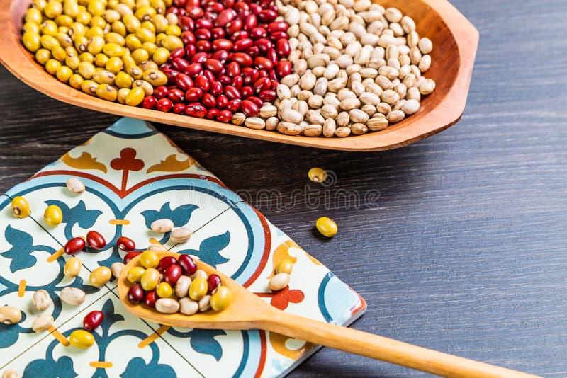 Variété de haricots sur la cuillère en bois sur le fond en bois fèves de mung, arachides, haricots rouges et haricots bruns photos libres de droits