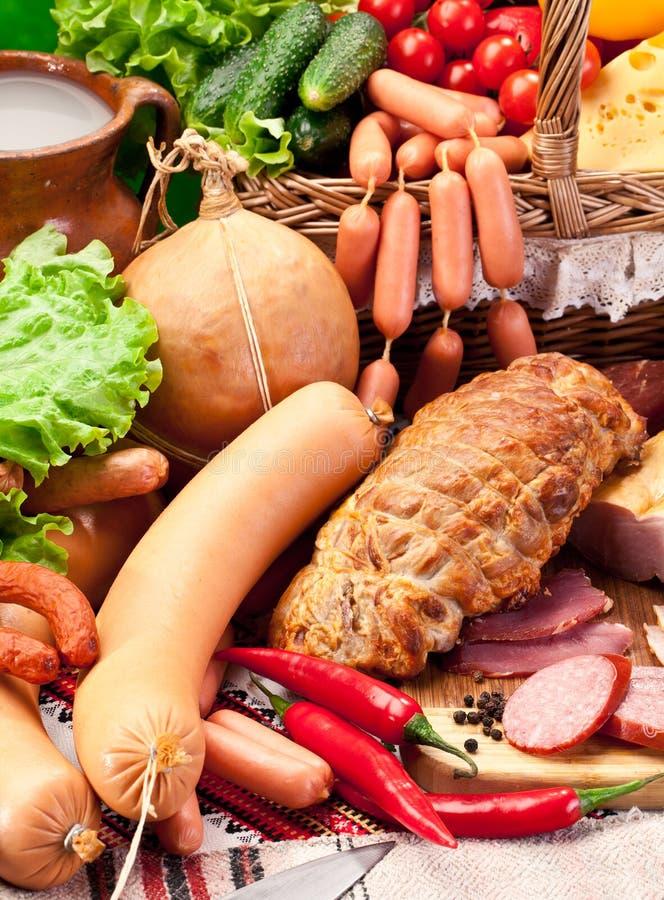 Variété de saucisses avec les produits de légume et laitiers. image stock