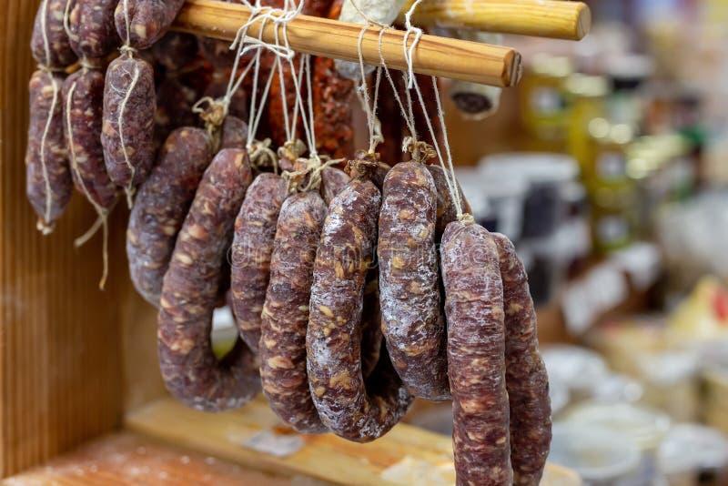 Variété de saucisses sèches délicieuses accrochées sur le support en bois au marché local d'agriculteur Épicerie fine savoureuse  images libres de droits