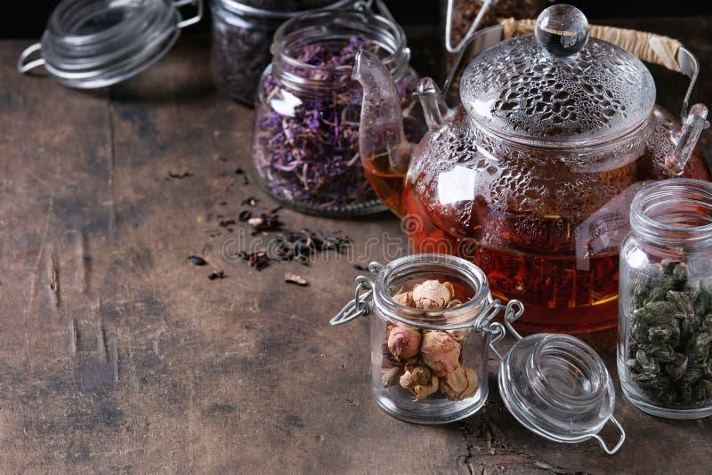 Variété de thé sec avec la théière photo stock