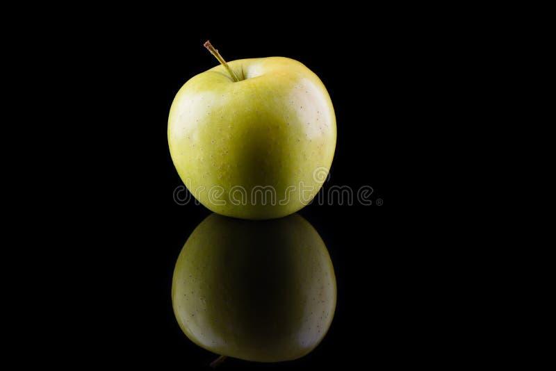 Variété verte de pomme d'or sur un fond noir avec la réflexion photo stock