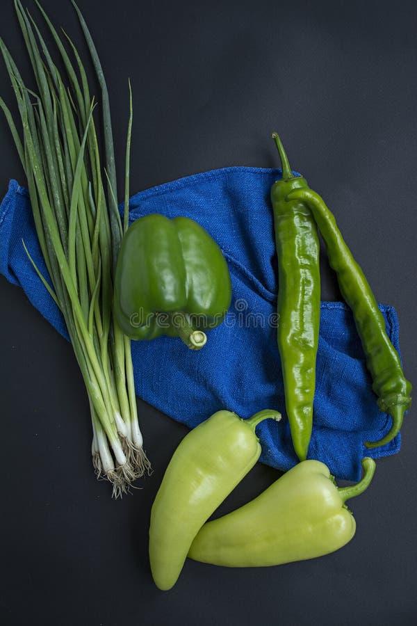 Variétés de poivrons Poivre bulgare, poivre de piment, oignons verts Poivrons doux et chauds Fond fonc? photos stock