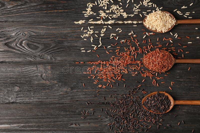 Variétés de riz brun dans des cuillères en bois sur la table, configuration plate images libres de droits