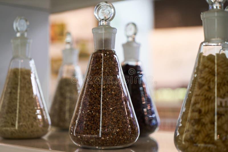 Vari cereali, grani, fagioli e pasta crudi per la cottura dell'alimento sano in barattoli di vetro su uno scaffale di legno immagini stock libere da diritti