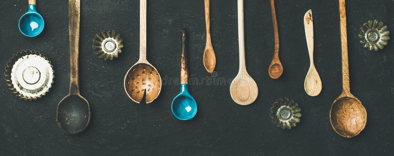 Vari cucchiai della cucina e muffe d'annata della teglia, vista superiore immagini stock