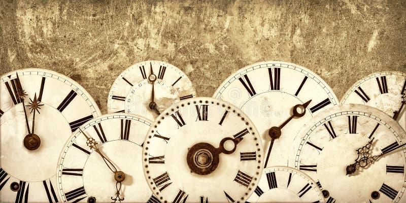 Vari fronti di orologio d'annata davanti ad una vecchia parete fotografia stock