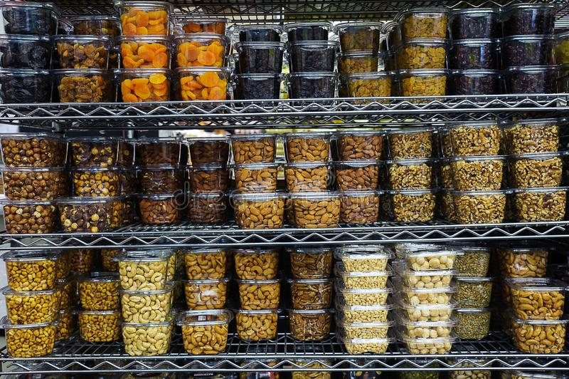 Vari frutta secca e dadi in recipienti di plastica che riempiono gli scaffali del metallo al suppermarket immagini stock libere da diritti