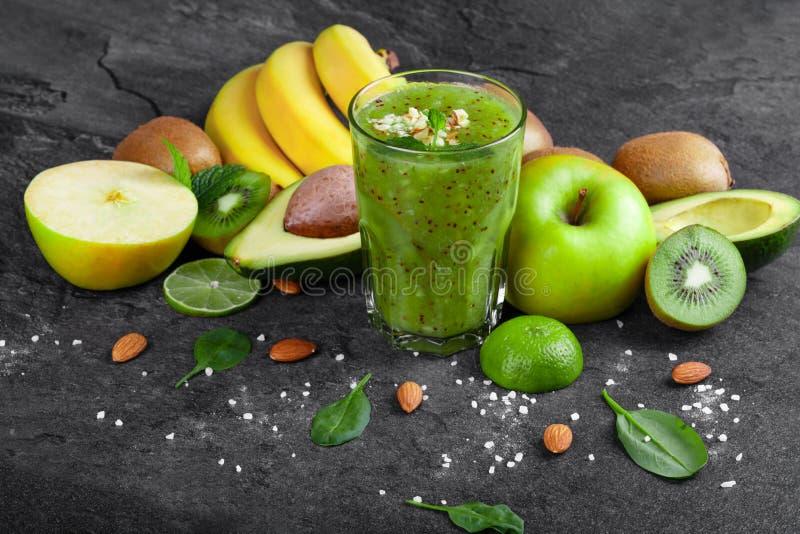 Vari frutti tropicali e frullato verde dal kiwi su un fondo grigio scuro Ingredienti nutrienti immagine stock