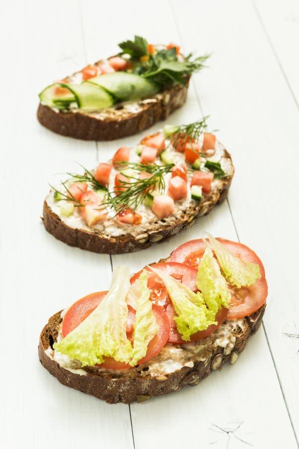 Vari generi di panini variopinti in una fila su un fondo di legno bianco Stile di vita e dieta sani verticale immagini stock